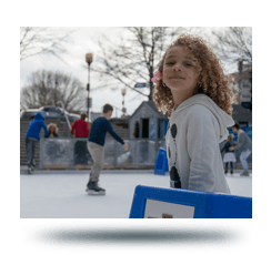 Girl overlooking ice rink with skaters in the background