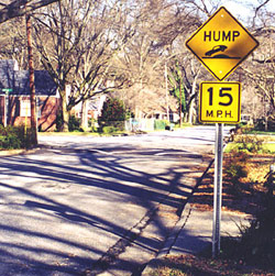 A neighborhood street with a hump traffic sign and a 15 mph traffic sign