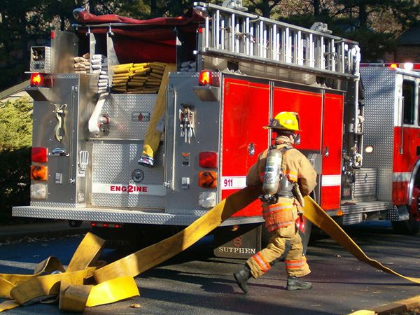 Firefighter hauling hose at the scene of a fire
